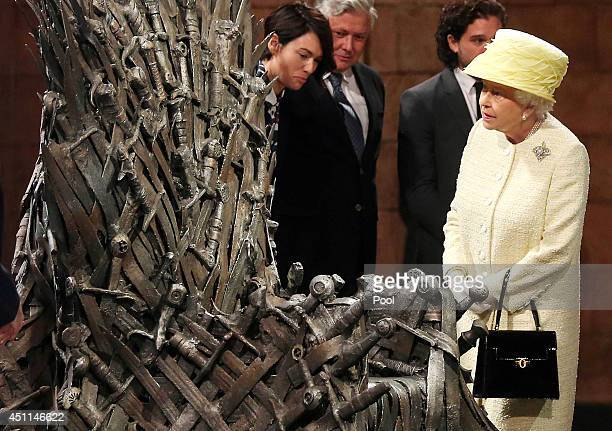 Queen Elizabeth II meets cast members of the HBO TV series 'Game of Thrones' Lena Headey and Conleth Hill as she views some of the props including...