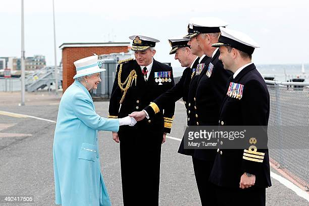 Queen Elizabeth II meets Commodore Paddy McAlpine as she arrives at Portsmouth Naval Base for a tour of the HMS Lancaster on May 20 2014 in...