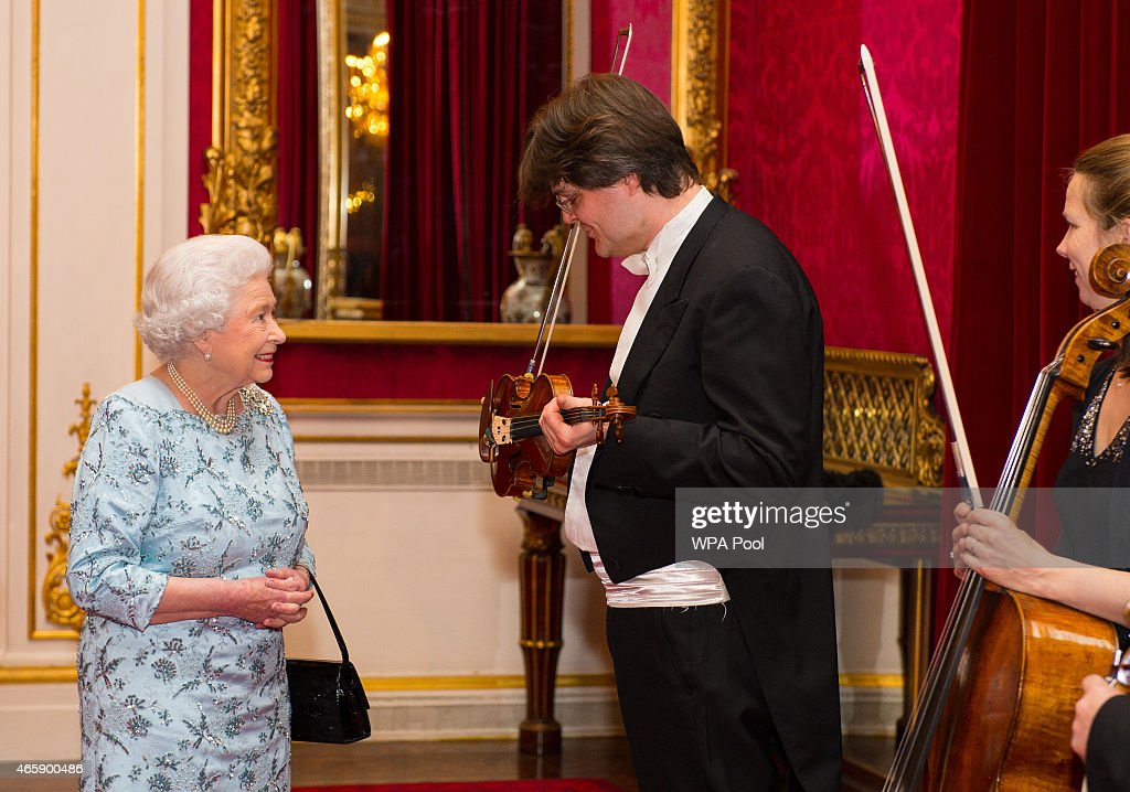 Queen Elizabeth II meets London Symphony Orchestra (LSO) violinist Roman Simovic, during a reception to mark the conclusion of the 'Moving Music' campaign and the long association of conductor Michael Tilson Thomas with the London Symphony Orchestra, at Buckingham Palace on March 11, 2015 in London, United Kingdom.