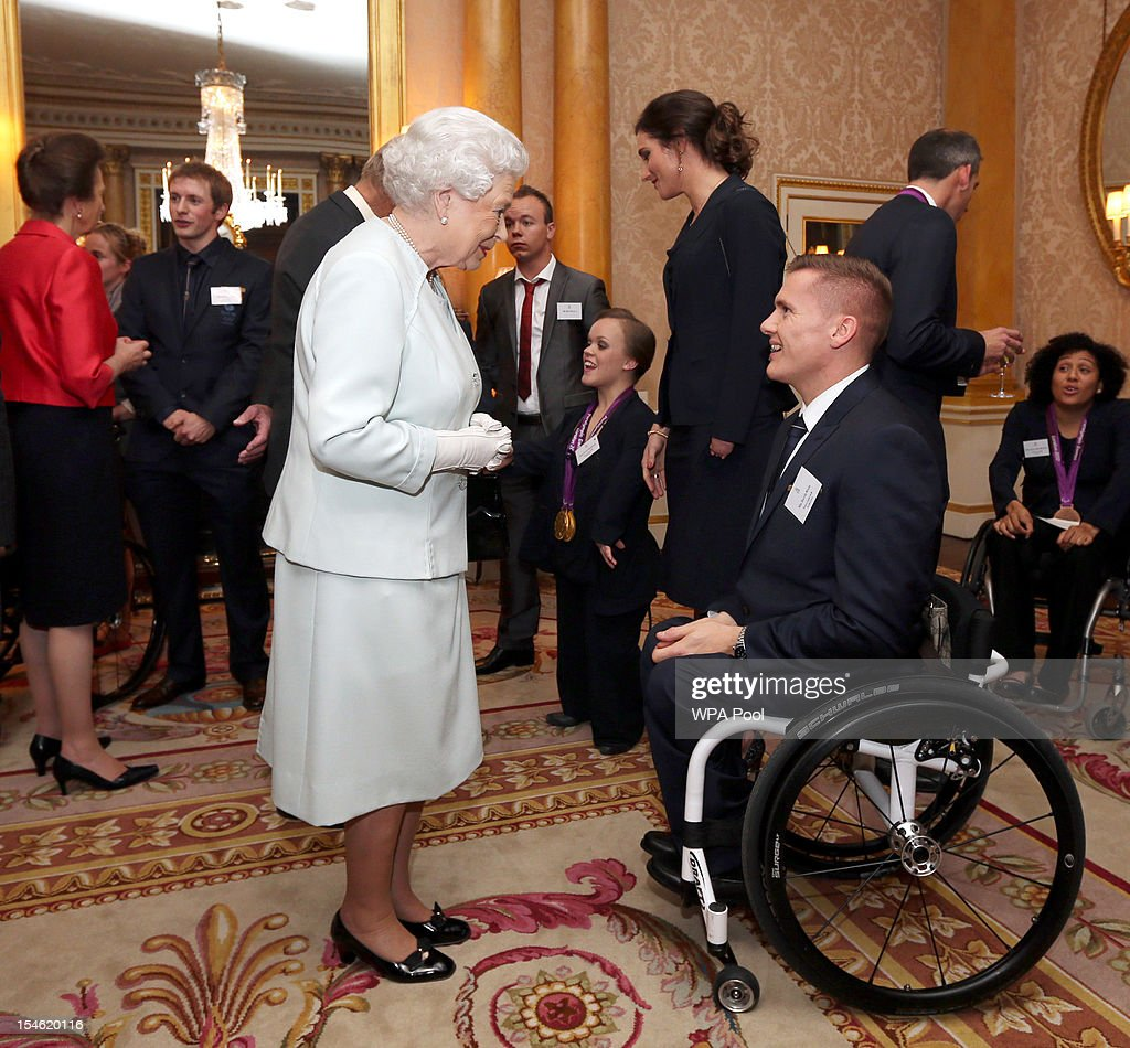 Queen Elizabeth II meets paralympian David Weir during a reception for the Team GB Olympic and Paralympic medalists at Buckingham Palace on October 23, 2012 in London, England.