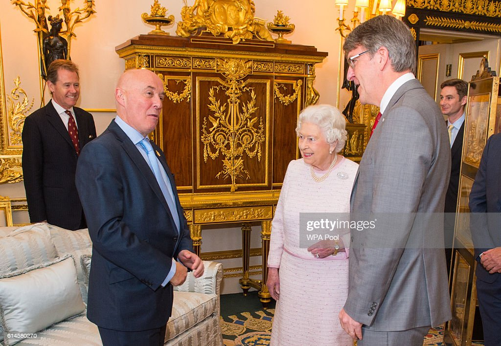 Queen Elizabeth II meets Red Cross Executive Director of Fundraising Mark Astarita (L) and Red Cross Chief Executive Michael Adamson, at the unveiling of a portrait of her by British artist Henry Ward, marking six decades of patronage to the British Red Cross, which has been unveiled at Windsor Castle on October 14, 2016 in Windsor, England. The Queen is the longest-serving patron of the charity, which supports people in crisis in the UK and overseas.