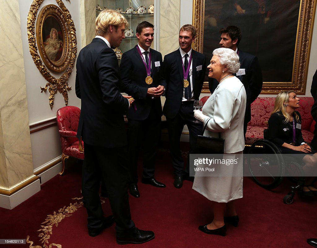 Queen Elizabeth II meets rowers Andrew Triggs-Hodge, Pete Reed, Alex Gregory and Tom James during a reception for the Team GB Olympic and Paralympic medalists at Buckingham Palace on October 23, 2012 in London, England.