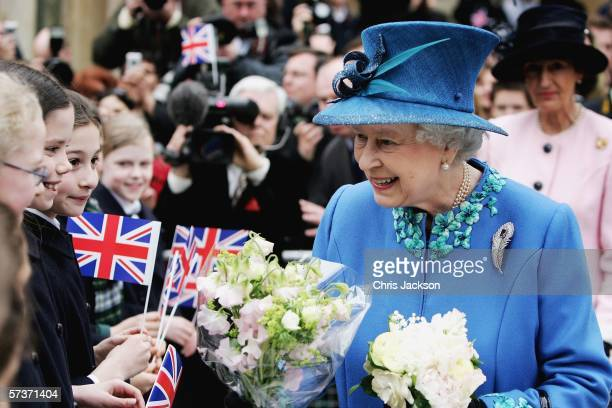 Queen Elizabeth II meets school children as she leaves BBC Broadcasting House to mark the anniversary of the granting of the Corporation's Royal...