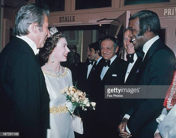 Queen Elizabeth II meets singer and performer Lovelace Watkins English television presenter and entertainer Bruce Forsyth South African actor and...