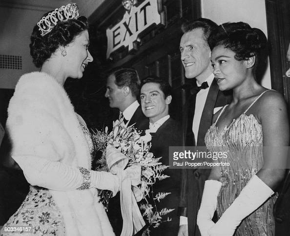 Queen Elizabeth II meets with American singer Eartha Kitt along with a lineup of stars including American singer Pat Boone Spanish dancer Antonio and...