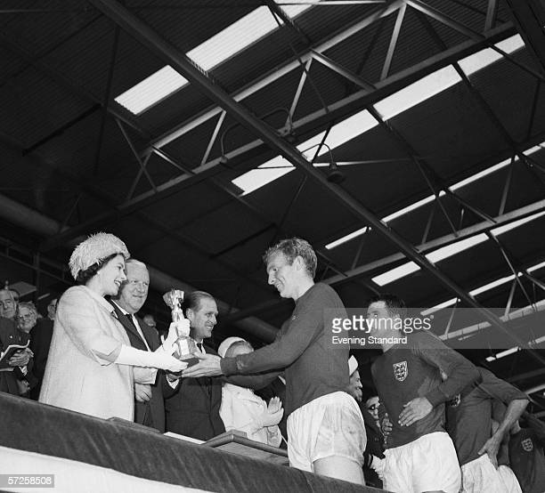 Queen Elizabeth II of Great Britain presenting the Jules Rimet trophy to the England captain Bobby Moore after the teams World Cup final victory over...