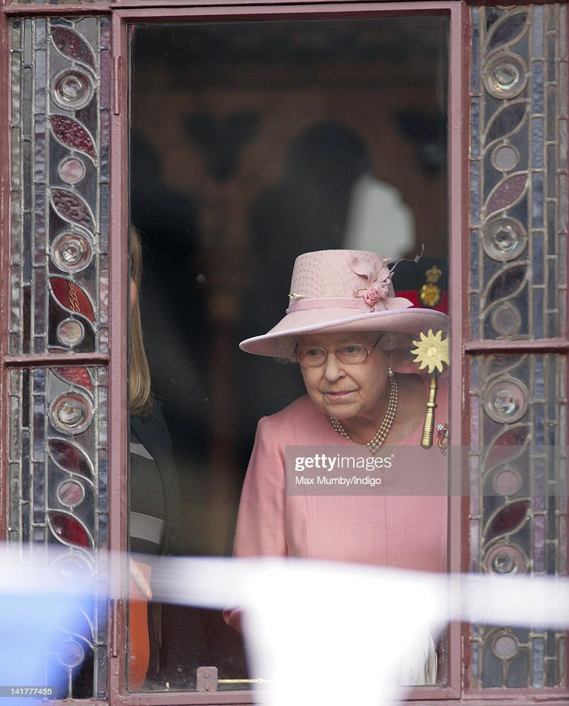 Queen <a gi-track='captionPersonalityLinkClicked' href=/galleries/search?phrase=Elizabeth+II&family=editorial&specificpeople=67226 ng-click='$event.stopPropagation()'>Elizabeth II</a> peers out of a window of Manchester Town Hall to view a Jubilee Garden during a visit to Manchester as part of her Diamond Jubilee Tour of the UK on March 23, 2012 in Manchester, England.