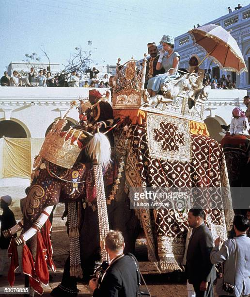 Queen Elizabeth II perches in a howdah on the back of an elephant at Benares during her tour of India 25th January 1961