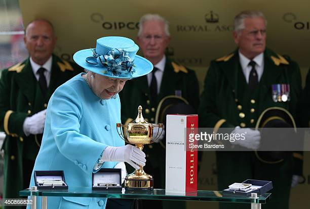 Queen Elizabeth II picks up the Gold Cup to present it to the connections of Leading Light after the Gold Cup on day three of Royal Ascot at Ascot...