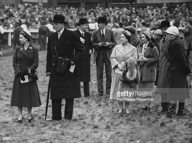 Queen Elizabeth II pictured left with Queen Elizabeth the Queen Mother and Princess Margaret along with the Royal jockey Dick Francis in the paddock...
