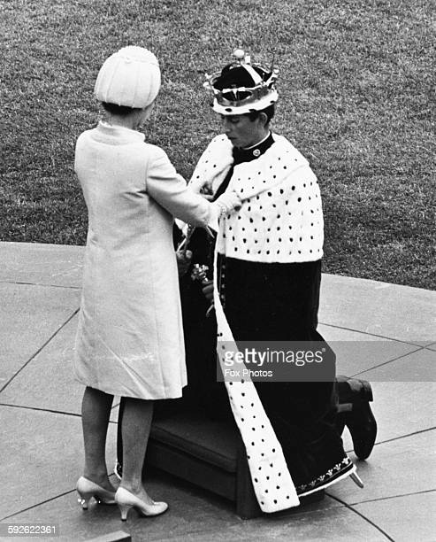 Queen Elizabeth II pinning the blue and ermine cape around the neck of Prince Charles as he is invested as the Prince of Wales at Caernarvon Castle...
