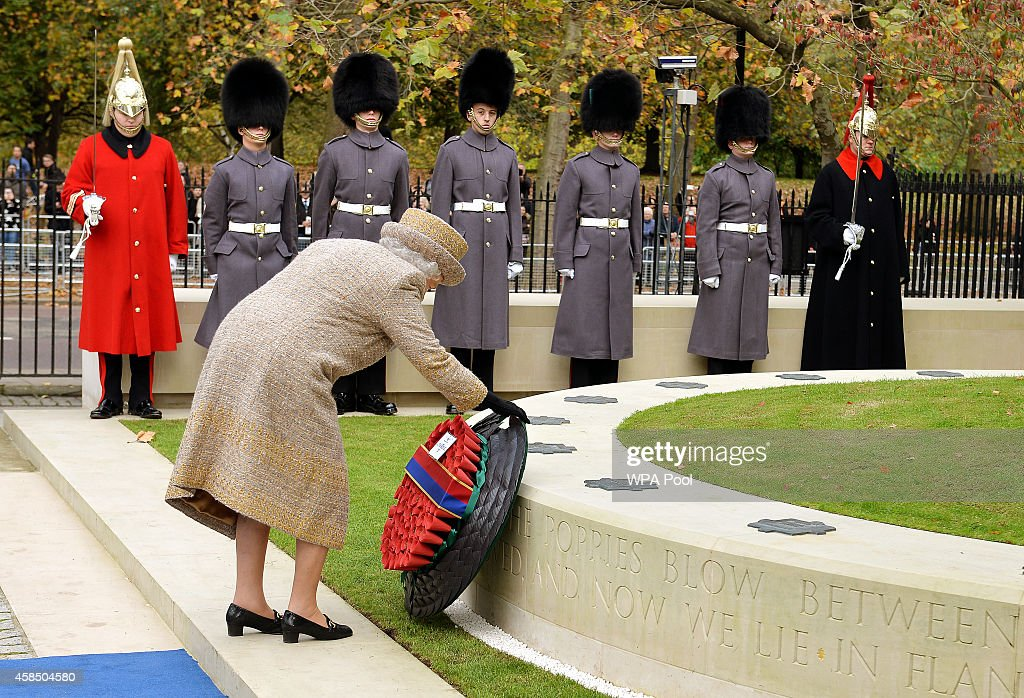 Queen Elizabeth II places a wreath of poppies at the new Flanders Field Memorial outside the Guards Chapel on November 6, 2014 in London, England.