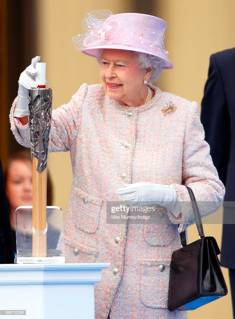 Queen Elizabeth II places her hand-written message to the Commonwealth into the 2014 Glasgow Commonwealth Games Baton during the launch of the Queen's Baton Relay at Buckingham Palace on October 9, 2013 in London, England. Following the launch, the baton relay will continue it's journey visiting all 70 competing nations and territories ahead of the 2014 Glasgow Commonwealth Games.