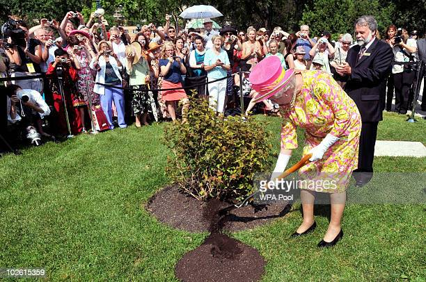 Queen Elizabeth II plants a tree in the garden of Government House where she also unveiled a statue of herself on July 3 2010 in Winnipeg Canada The...