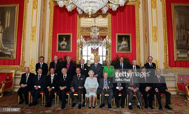 Queen Elizabeth II poses for a group photo with the Order of Merit members Mr Neil MacGregor The Rt Hon Jean Chretien Lord Eames Sir Michael Howard...