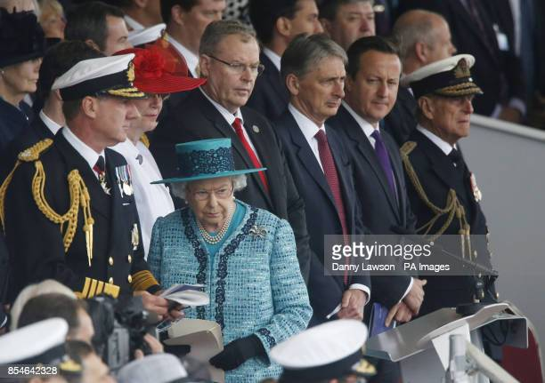 Queen Elizabeth II prepares to deliver a speech while the Duke of Edinburgh Prime Minister David Cameron and Defence Secretary Philip Hammond look on...