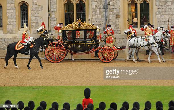 Queen Elizabeth II prepares to exit the state carriage whilst greeting the Emir of the State of Qatar Sheikh Hamad bin Khalifa AlThani and his...