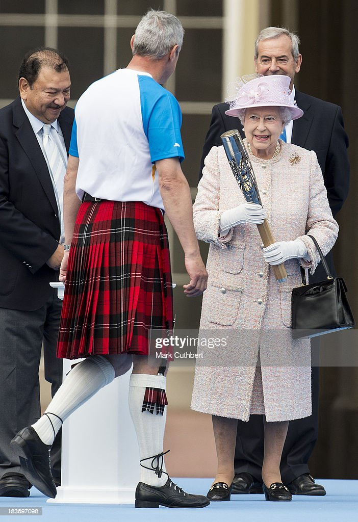 Queen Elizabeth II prepares to hand the baton to former Scottish athelete and Olympic gold medallist Alan Wells during The Baton Relay for the 2014 Commonwealth Games at Buckingham Palace on October 9, 2013 in London, England.
