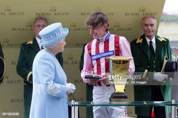 Queen Elizabeth II present Jockey of Lethal Force Adam Kirby after winning the Diamond Jubilee Stakes during day five of the Royal Ascot meeting at...