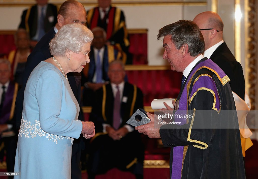 Queen Elizabeth II presents a Queen's Anniversary Prize for Higher and Further Education Award to Nigel Carrington of University of the Arts London at Buckingham Palace on February 27, 2014 in London, England.