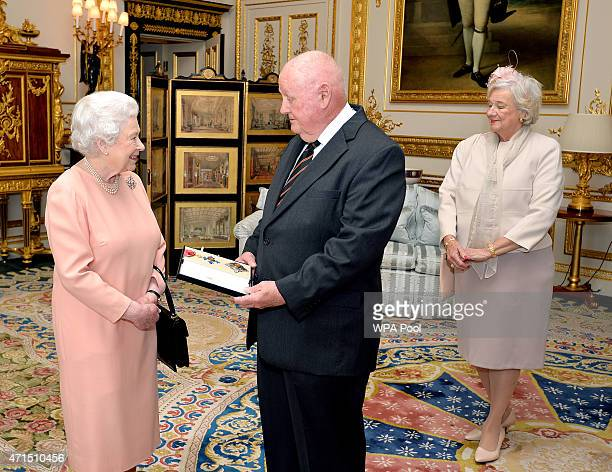 Queen Elizabeth II presents American businessman John Mars with an honorary Knighthood at Windsor Castle on April 29 2015 in Windsor England