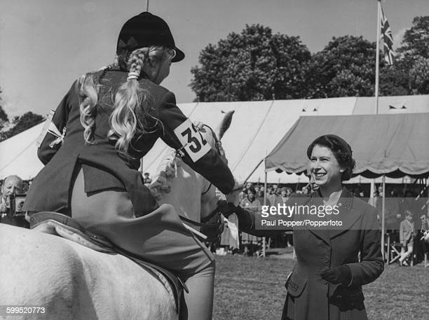 Queen Elizabeth II presents an award to little Marigold Peddie on her grey mare 'Dainty Dinner' after winning the Child's Pony Class at the Royal...
