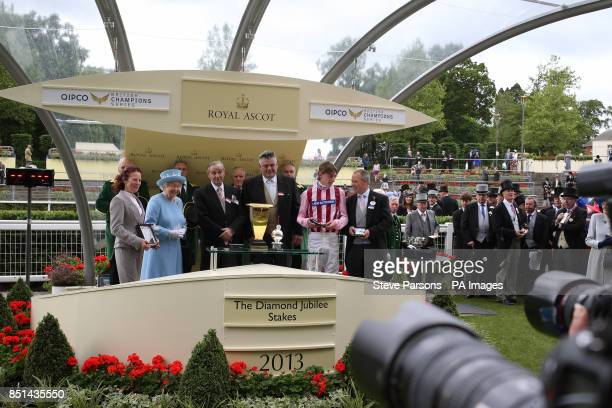 Queen Elizabeth II presents Diamond Jubilee Stakes trophy to jockey Adam Kirby after he won riding Lethal Force during day five of the Royal Ascot...
