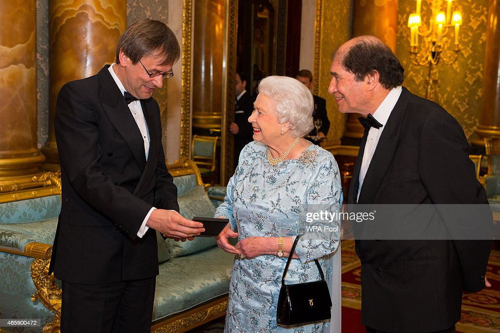 Queen Elizabeth II presents Simon Halsey (left) with the 2014 Queen's Medal for Music, accompanied by Lord Berkeley, representing the Master of the Queen's Music, during a reception to mark the conclusion of the 'Moving Music' campaign and the long association of conductor Michael Tilson Thomas with the London Symphony Orchestra, at Buckingham Palace on March 11, 2015 in London, United Kingdom.