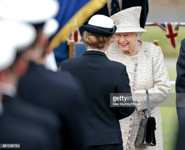 Queen Elizabeth II presents The Queen's Gold Medal to a student after watching a parade during a visit to Pangbourne College to celebrate it's...