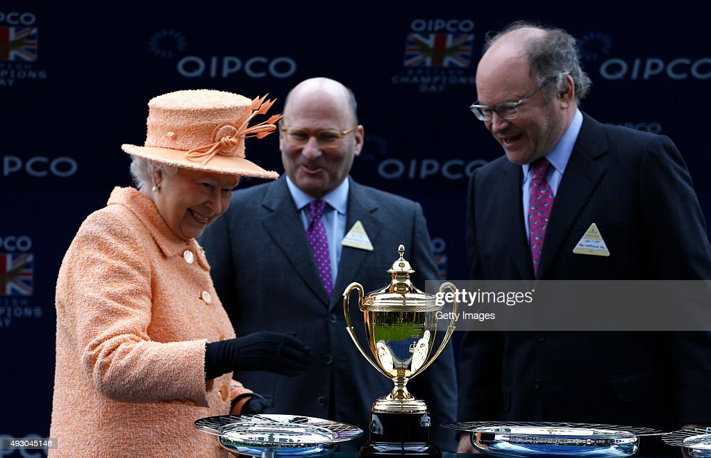Queen Elizabeth II presents the trophy to owners Alain Wertheimer and Gerard Wertheimer, after their horse Solow won the Queen Elizabeth II Stakes Race run during the QIPCO British Champions Day at Ascot Racecourse on October 17, 2015 in Ascot, England.