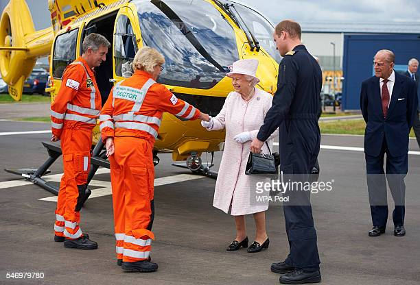 Queen Elizabeth II Prince Philip Duke of Edinburgh and Prince William Duke of Cambridge speak with crew members as she is given a tour while opening...