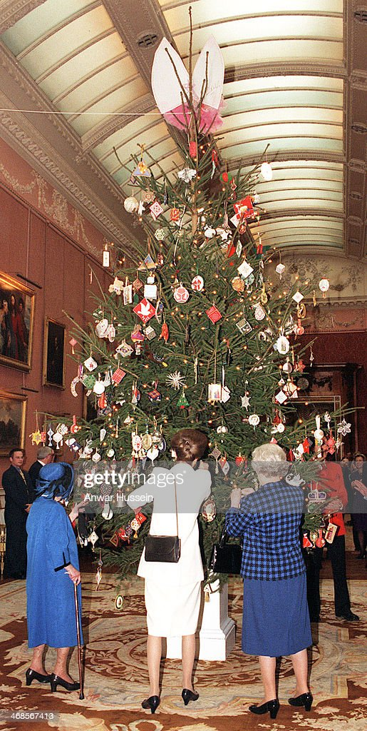 Queen Elizabeth II, Princess Anne, the Princess Royal and Queen Elizabeth, The Queen Mother admire Christmas decorations on the Christmas tree in the Picture Gallery at Buckingham Palace after meeting representatives of a group of celebrity and amateur embroiderers who have made some 500 embroidered ornaments for The Queen's Christmas Tree on December 15, 1998 in London, England.