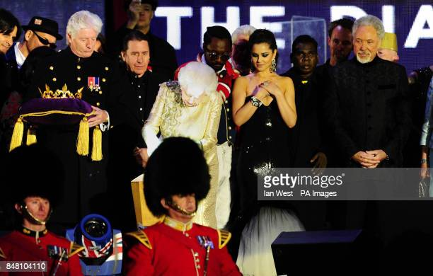 Queen Elizabeth II pushes the button on stage to light the Jubilee Beacons at the end of the Diamond Jubilee Concert at Buckingham Palace