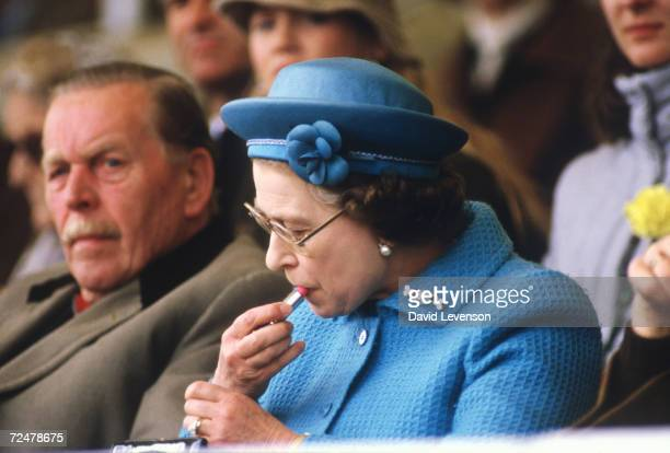 Queen Elizabeth II puts on lipstick in the Royal Box at the Windsor Horse Show on May 11 1985 Prince Phillip was about to enter the dressage ring...