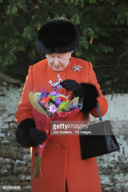 Queen Elizabeth II receives a bouquet of flowers and piece of origami after the traditional Christmas Day church service at St Mary Magdalene Church...