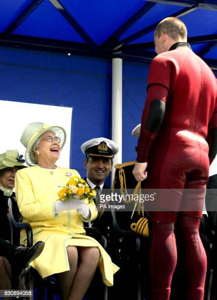 Queen Elizabeth II receives a bouquet of flowers from a naval diver playing the role of a VIP who had been 'rescued' and brought back to the aircraft...