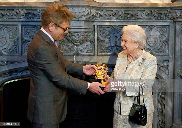 Queen Elizabeth II receives an honorary BAFTA from actor Kenneth Branagh in recognition of a lifetime's support to British Film and Television at...