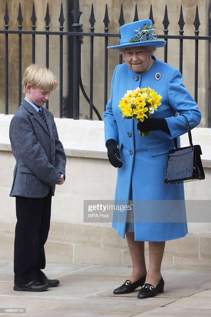 Queen Elizabeth II receives flowers as she leaves the Easter Sunday service at St George's Chapel at Windsor Castle on April 5, 2015 in Windsor, England.