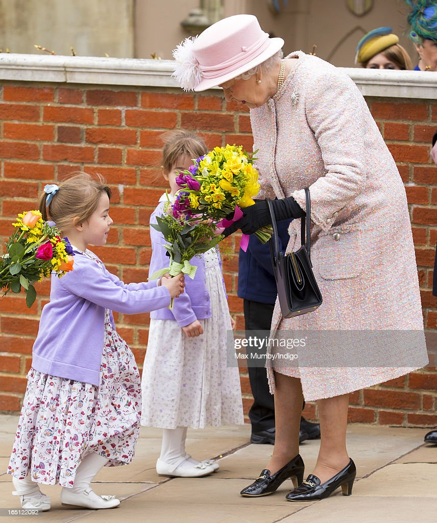 Queen Elizabeth II receives flowers from a young girl as she attends the Easter Matins Church Service at St George's Chapel, Windsor Castle on March 31, 2013 in Windsor, England.