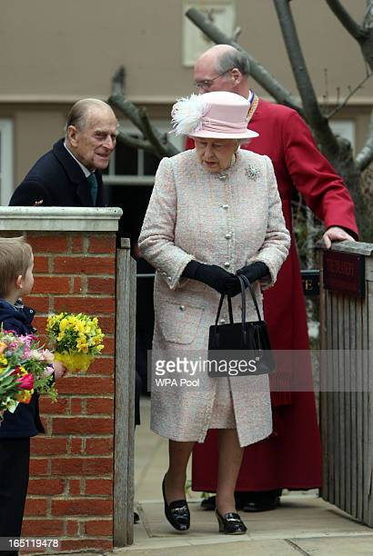 Queen Elizabeth II receives flowers from local children as she and Prince Philip Duke of Edinburgh leave the Easter Day service at St George's Chapel...