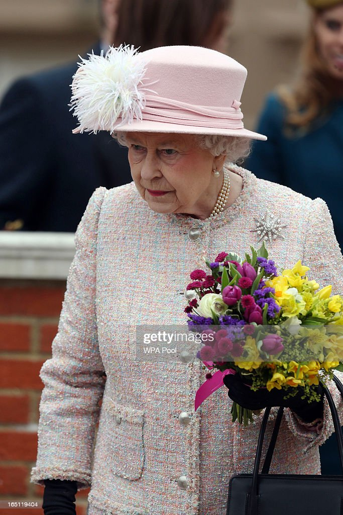 Queen Elizabeth II receives flowers from local children as she leaves the Easter Day service at St George's Chapel in the grounds of Windsor Castle on March 31, 2013 in Windsor, England.