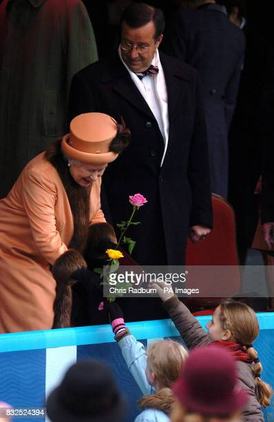 Queen Elizabeth II receives flowers from two children shortly before a concert in Town Hall Square Tallinn Estonia as the President of Estonia Toomas...