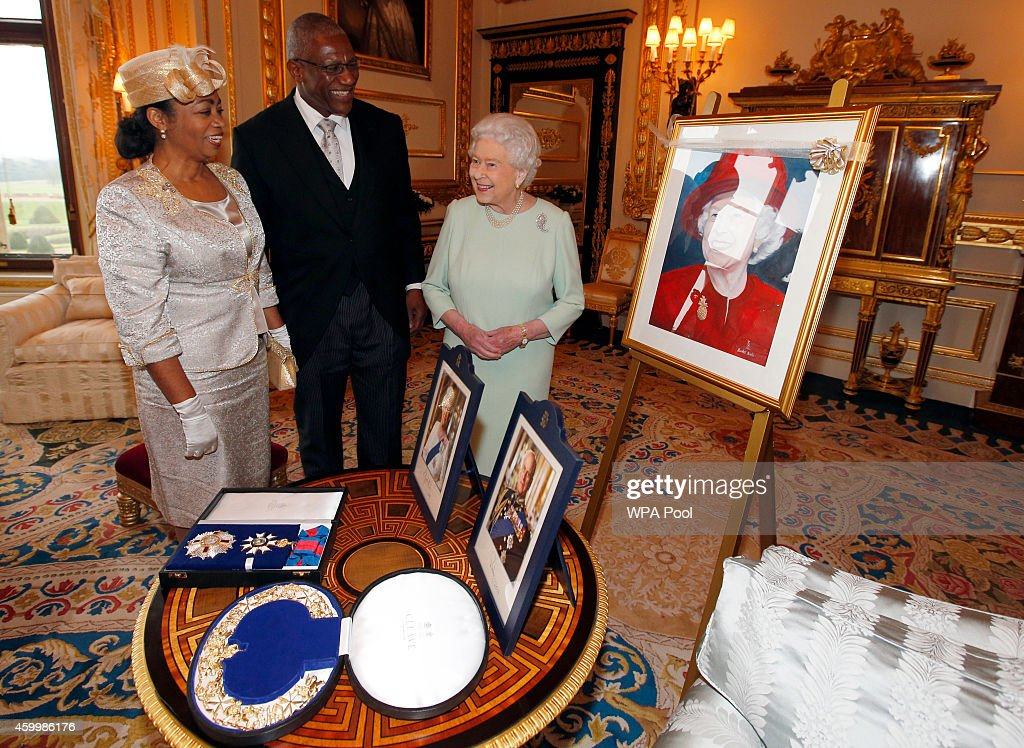 Queen Elizabeth II receives the gift of a portrait from Sir Rodney Williams and his wife upon his appointment as Governor-General of Antigua and Barbuda during an audience at Windsor Castle on December 5, 2014 in Windsor, United Kingdom.