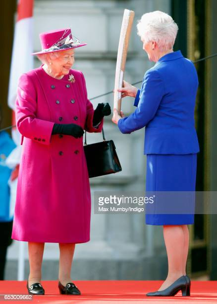 Queen Elizabeth II receives The Queen's Baton from Louise Martin President of the Commonwealth Games Federation as they attend the launch of The...