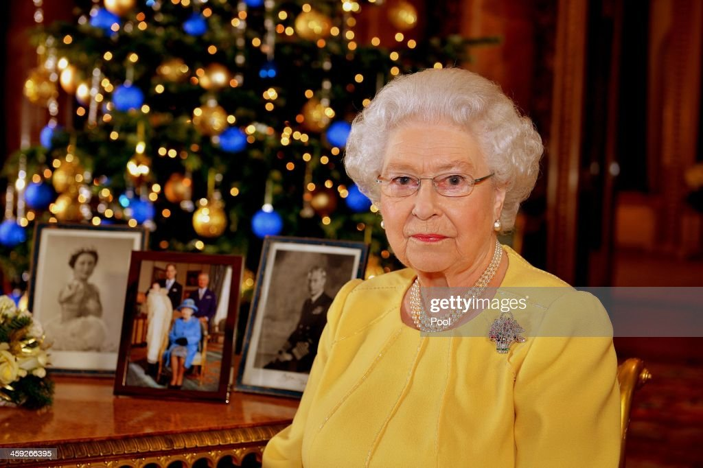 Queen Elizabeth II records her Christmas message to the Commonwealth, in the Blue Drawing Room at Buckingham Palace on December 12, 2013 in London England. Broadcast on December 25, 2013, the Queen wears a diamond, ruby and sapphire brooch given to her by her parents to celebrate the birth of Prince Charles in 1948. By her side are photographs of her parents, King George VI and Queen Elizabeth - The Queen Mother, and also a picture from this years christening of Prince George of Cambridge.