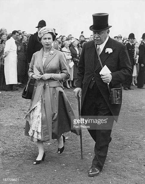 Queen Elizabeth II returning from the paddock with politician and racehorse owner Harry Primrose 6th Earl of Rosebery at the Derby Epsom Downs...