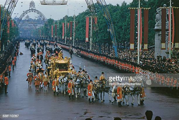 Queen Elizabeth II rides in the Gold State Coach towards Buckingham Palace past crowds of spectators lining the Mall during her Coronation procession...