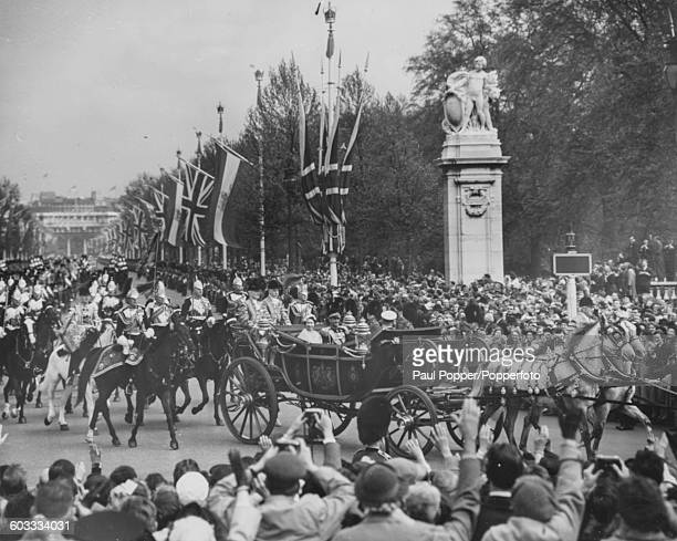 Queen Elizabeth II rides in the State Coach with Mohammad Reza Pahlavi Shah of Persia along the Mall towards the Victoria Memorial in London during a...