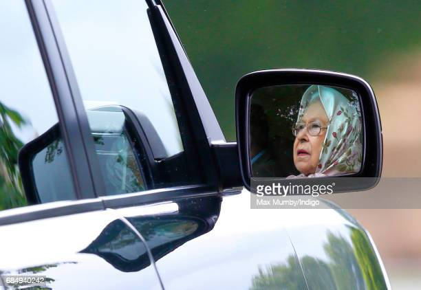 Queen Elizabeth II seen reflected in the wing mirror of her Range Rover car as she drives around the Royal Windsor Horse Show in Home Park on May 12...