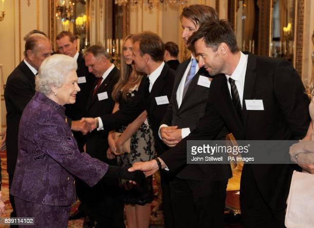 Queen Elizabeth II shakes hands with actor Hugh Jackman in the white drawing room at Buckingham Palace before a Royal reception for members of the...